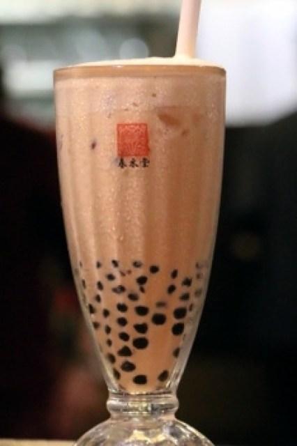 台湾名物のタピオカミルクティー。グラスの底のタピオカの粒々をストローで飲む=西本秀撮影