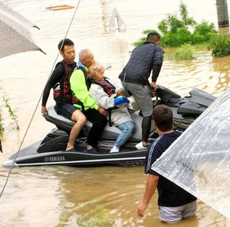内藤翔一さん(バイクの前席)たちに水上バイクで救助される住民=7日、岡山県倉敷市真備町、富田育海さん撮影