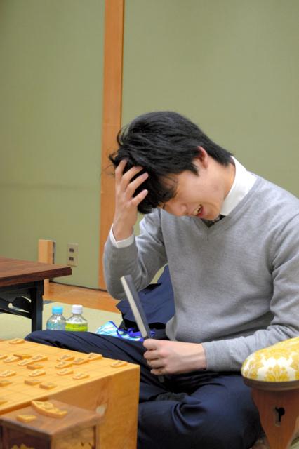 感想戦で頭を抱えて笑顔を見せた藤井聡太七段=大阪市の関西将棋会館、佐藤圭司撮影