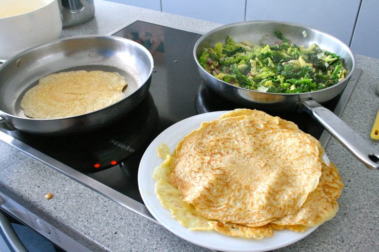 A plate of crepes next to pans of crepe and a cabbage and bacon filling on the hob