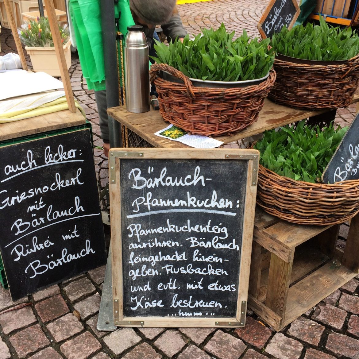 Wild garlic stand at farmers' market with chalk board