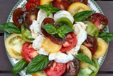A large green patterned plate with mozzarella, tomato and basil salad on it