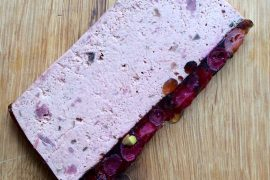 Wild boar pâté with a cranberry and pistachio jelly on a wooden board