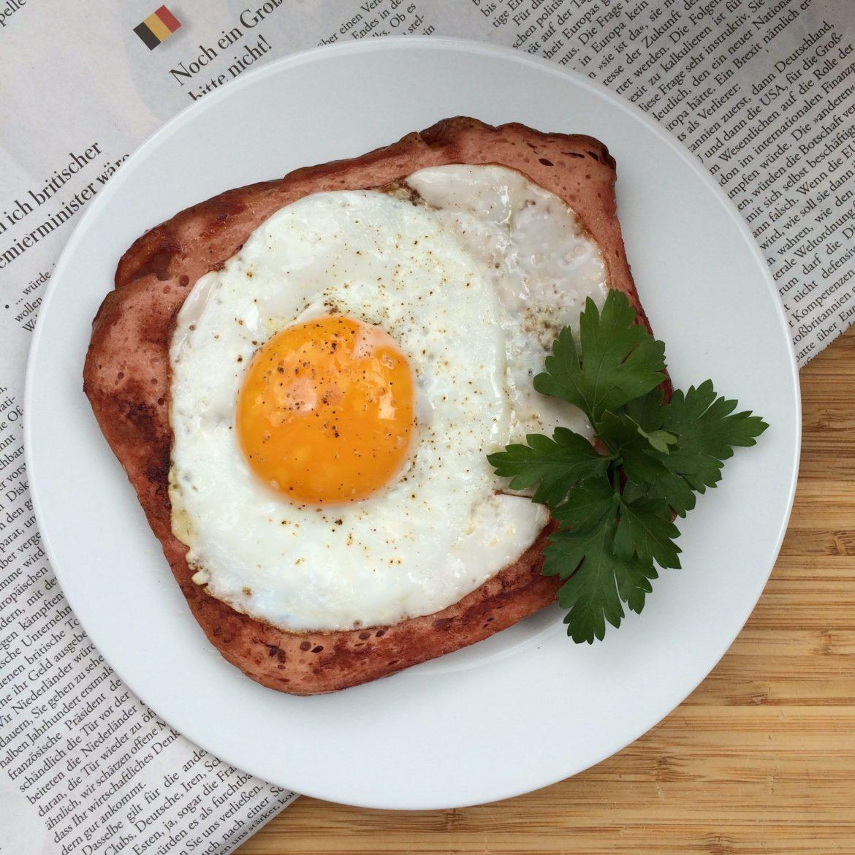 A slice of Leberkäse with a fried egg on top