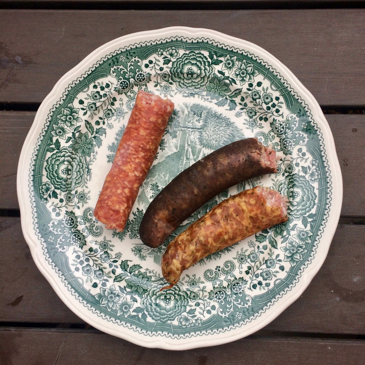 Three half-eaten German Mettwurst sausages on a green patterned plate