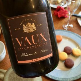 Bottle of Vaux sparkling wine in front of a plate of French macarons