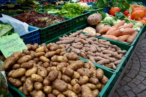 Potatoes, carrots and other vegetables in crates at a German market