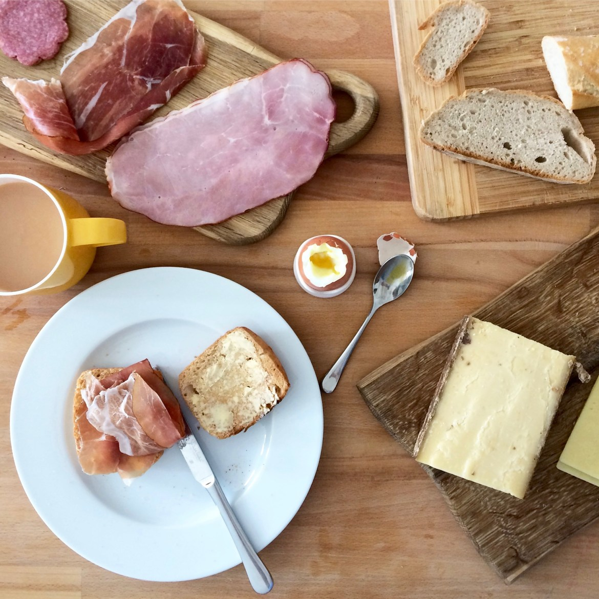 Flatlay of a German breakfast with meats, cheeses, bread and a boiled egg
