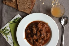 Flat lay of Wiener Gulasch with bread, apple juice and cutlery
