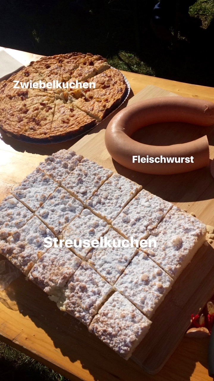 An Instagram Story snap of Streuselkuchen, Zwiebelkuchen and Fleischwurst on a table during a wine tasting tour
