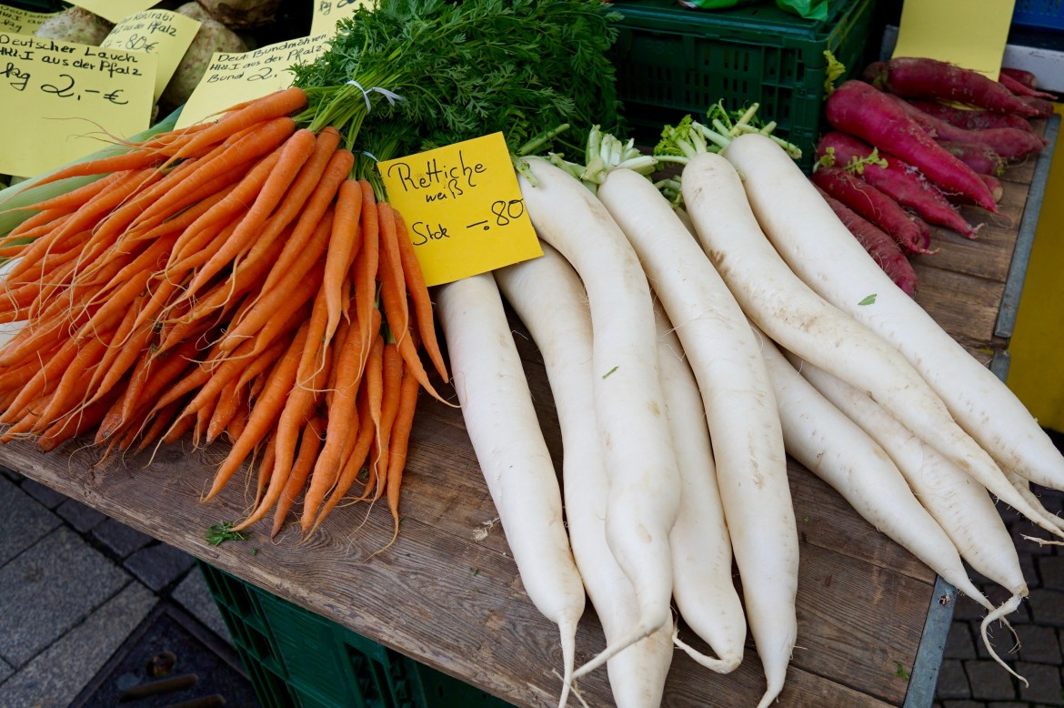 Carrots and long white radishes on display at a farmers' market in Germany