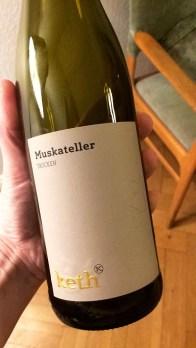 A hand holding a bottle of Keth Muskateller