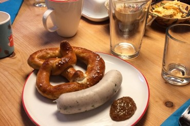 A white plate with a Pretzel, Weisswurst and Bavarian sweet mustard on a breakfast table in Munich