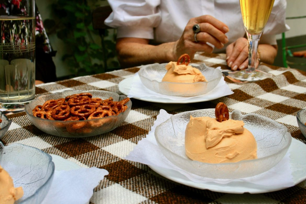 Two bowls of Spündekäse and a bowl of Pretzels on a plaid tablecloth