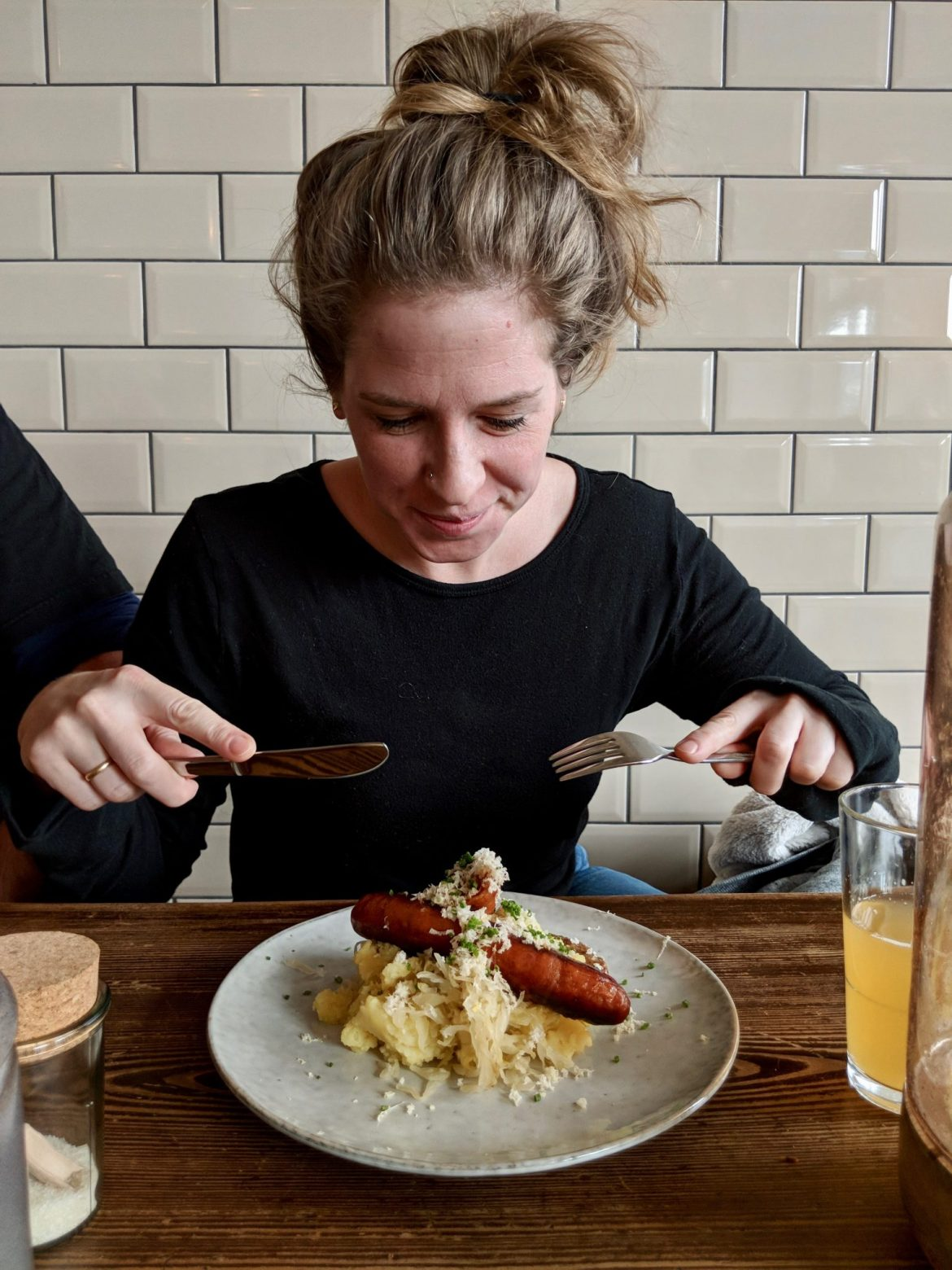 Christie Dietz eating sausages on a white plate and wooden table against a tiled backdrop