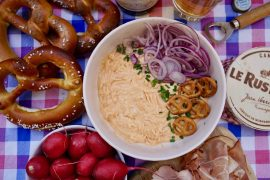 A flatlay of Obatzda in a bowl with pretzels, red onion, radishes and ham