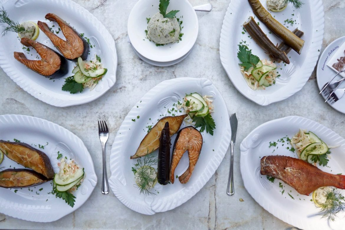 Flat lay of various smoked fish dishes on a marble table