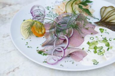 A white plate of pink soused herring with red onion and dill