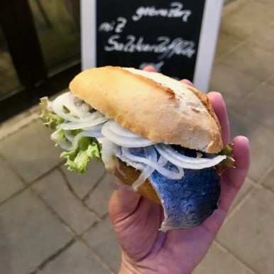 A hand holding up a white bread roll stuffed with pickled herring, lettuce and sliced white onion