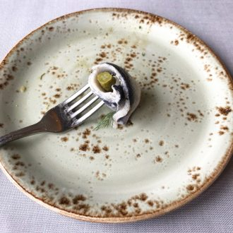 A rollmop on a fork on a speckled plate
