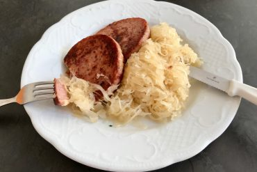 Two slices of fried Saumagen with Sauerkraut on a white plate