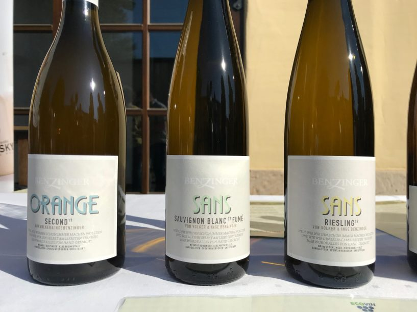 Three bottles of natural wine on a white tablecloth