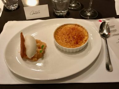 Crème brûlée on a white plate with ice cream and stewed apples