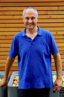 A man in a blue pol shirt standing in front of a wooden building and large crate of apples