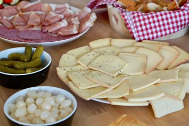 A table filled with plates of raclette cheese, meat, bread, silver onions and cornichons