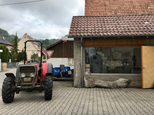 A stone and wooden building with a red tractor parked outside
