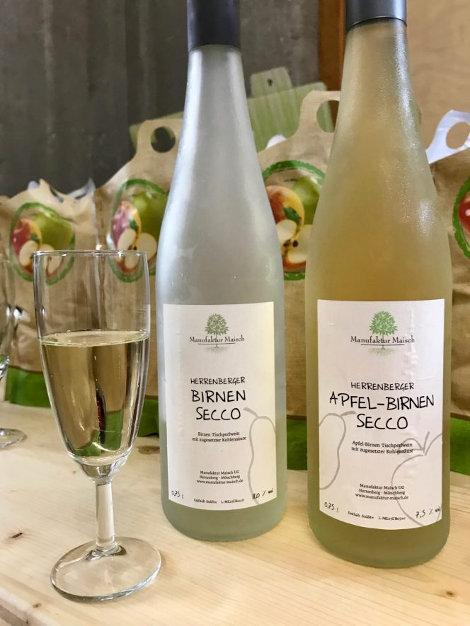A glass and two bottles of fruit secco