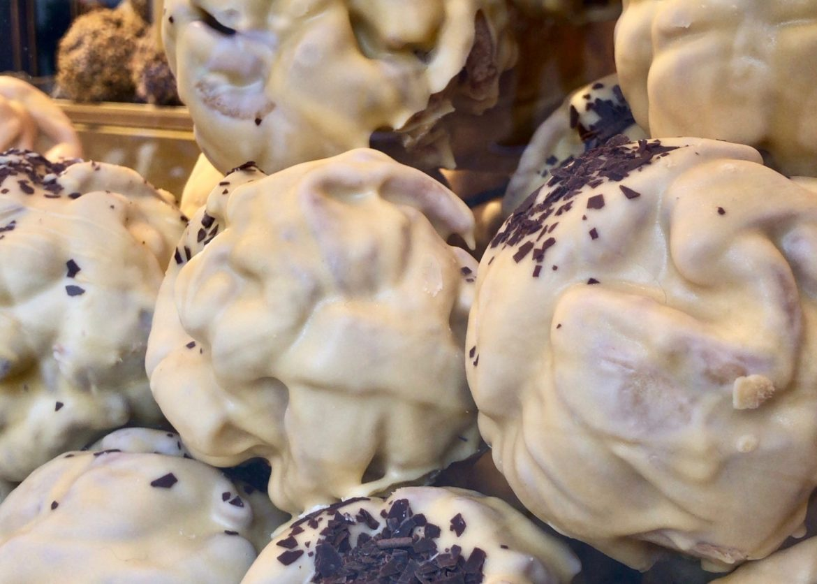 White chocolate-covered Schneebällchen behind glass at a Christmas market