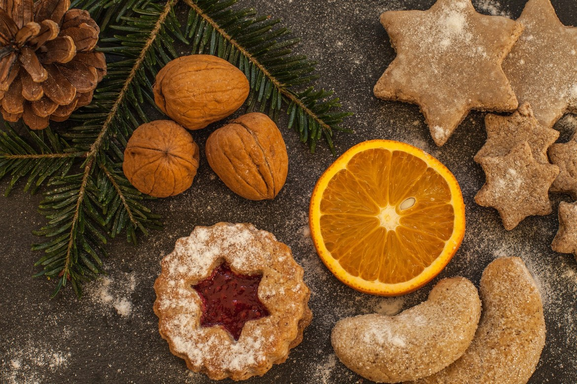 A flat lay photograph of Christmas cookies with walnuts and a slice of orange