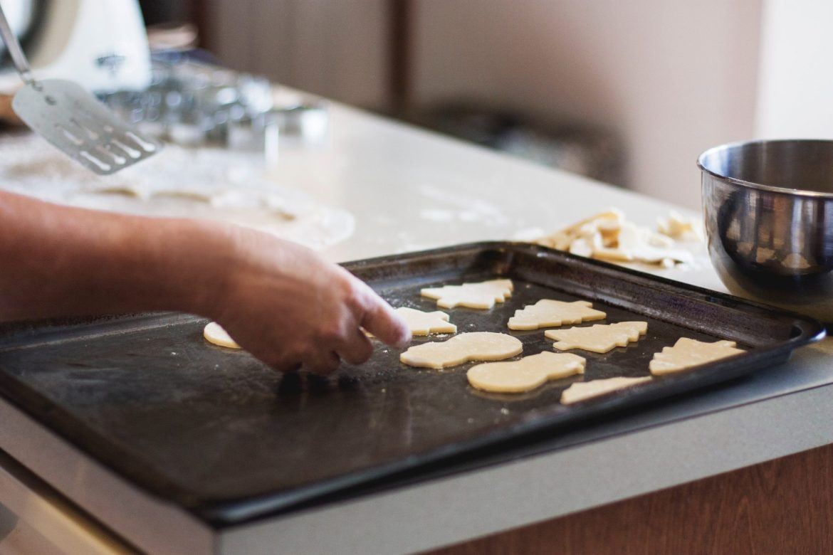 Raw cookies being placed on a baking tray