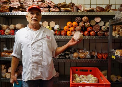 Wolfgang Hardt showing off sausages in his walk-in butcher's fridge