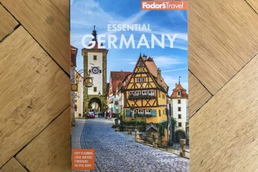 Copy of Fodor's Essential Germany guide book lying on a wooden floor
