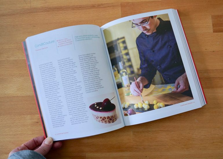 A book about bakeries open at a page with writing and a picture of a man working with patisserie