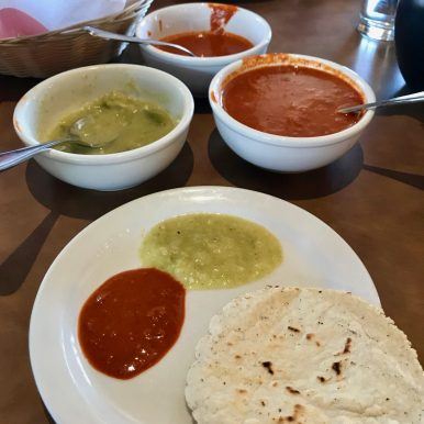 Red and green chile sauces on a white plate with a corn tortilla