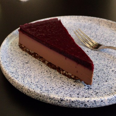 A slice of chocolate raspberry torte on a grey speckled plate