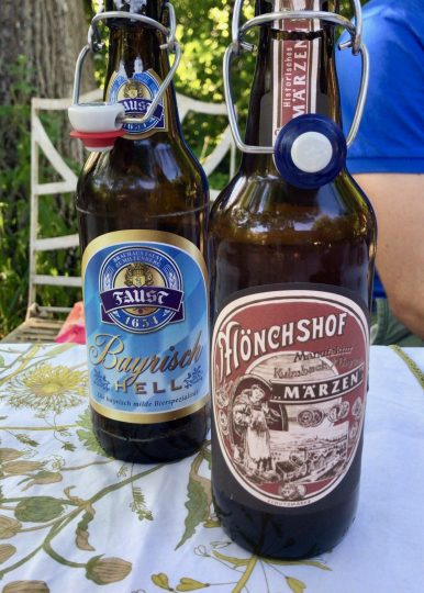 Two bottles of German beer on a white tablecloth table outside
