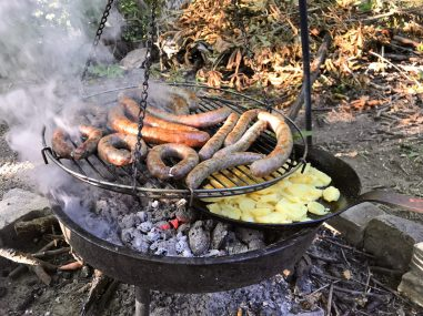 A cast iron pan filled with sliced potatoes underneath a swinging grill full of sausages