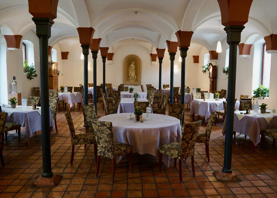 The interior of the wine tavern at Domäne Mechtildshausen with round tables and arched ceilings