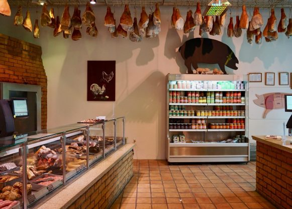 Butchers counter and hams air-drying from the ceiling at Domäne MEchtildshausen