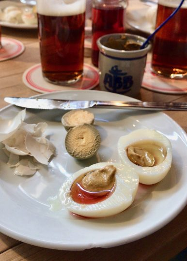 Two halves of a pickled egg filled with mustard, oil and vinegar at the Uerige in Düsseldorf