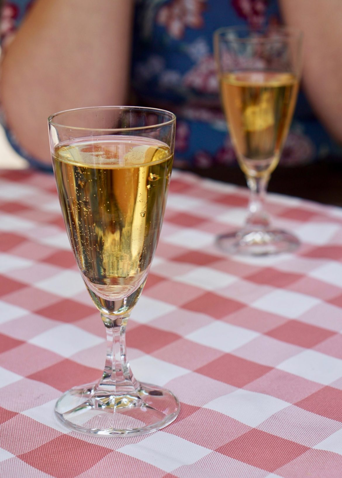 Two fluted glasses of Apfelsecco on a red and white checked tablecloth