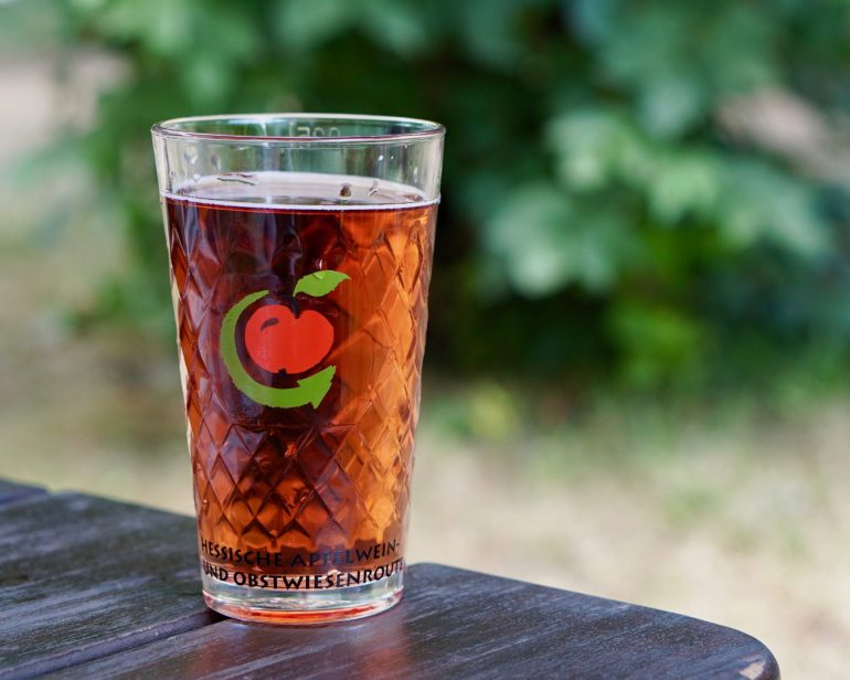 A glass of rosé Apfelwein on a wooden table against a leafy background