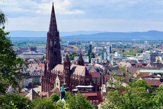 View of Freiburg with red church, square and lots of trees with the mountains behind