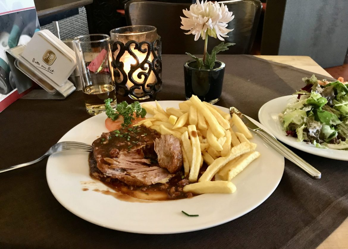 Trierer Spießbraten on a white plate with fries and a salad garnish