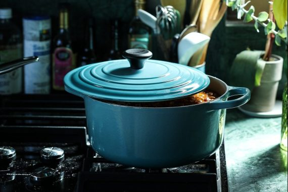 Blue Le Creuset dish with lid on on a stove