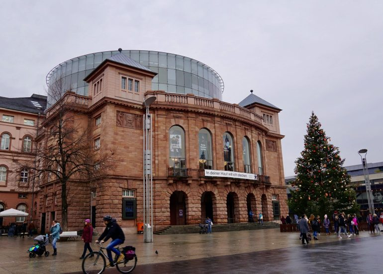 The large, curved facade of the State Theater in Mainz with a Christmas tree next to it